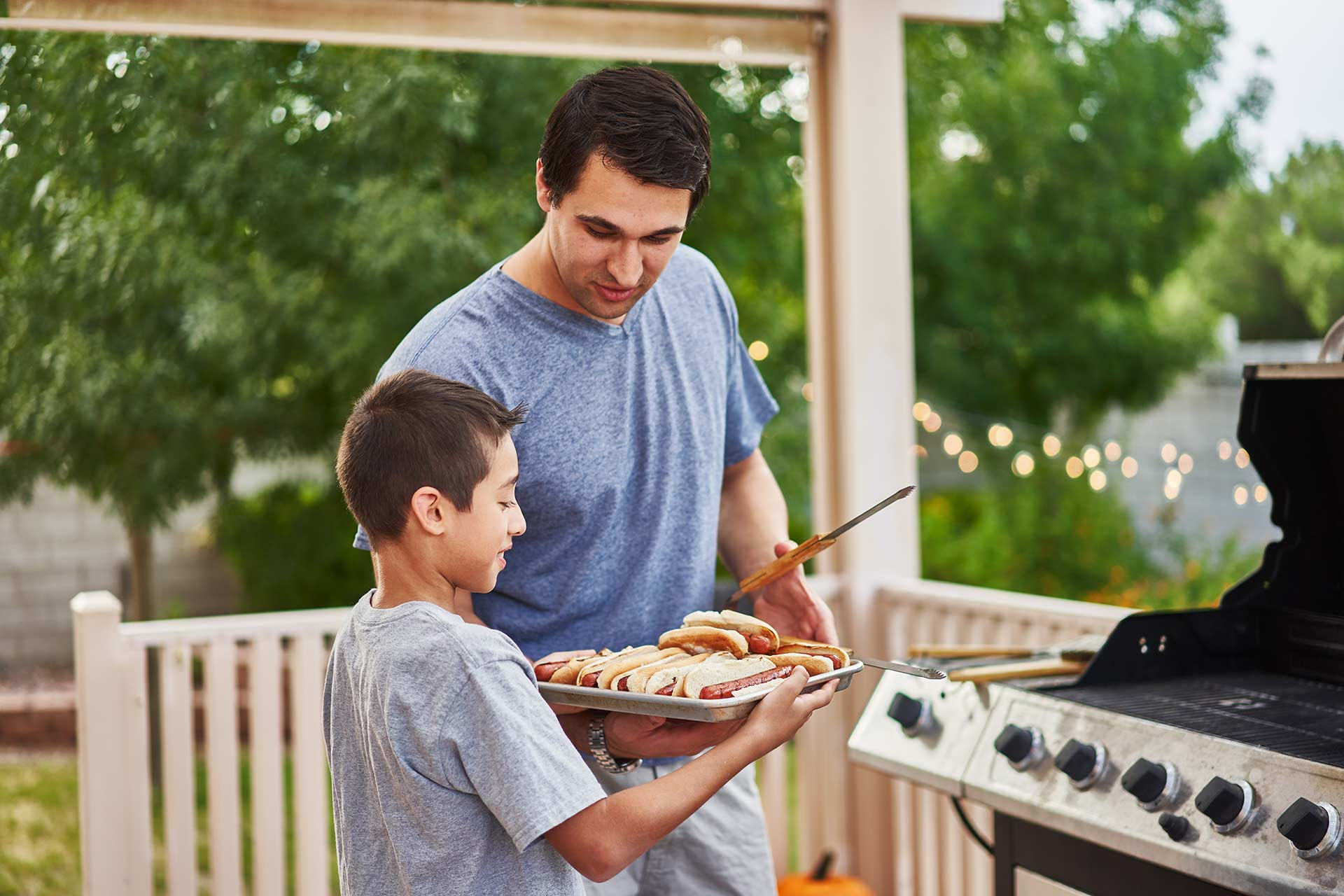 father and son grilling hot dogs