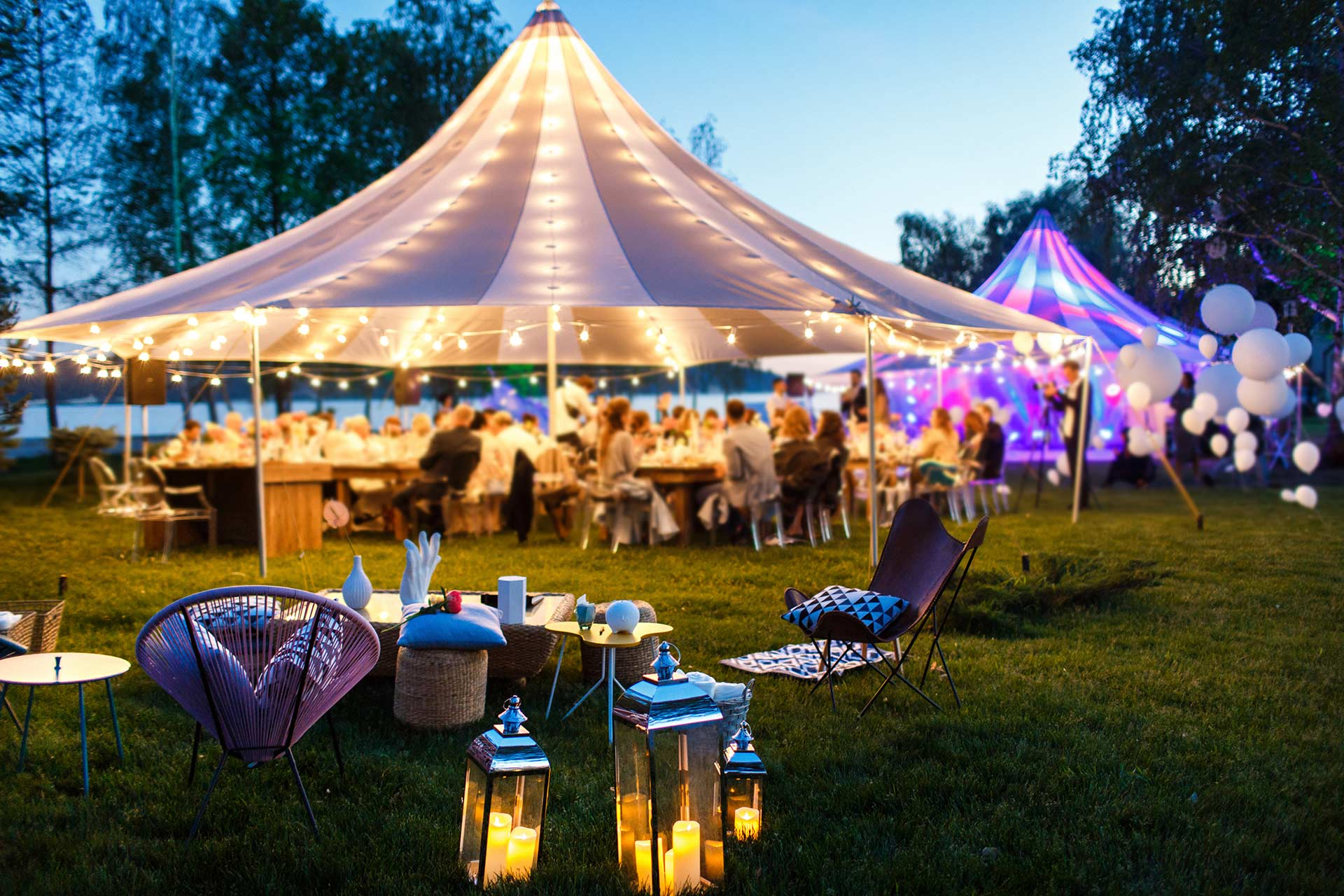 an outdoor party with lighted tents